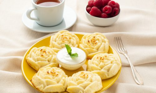 diet-cheese-pancakes-rose-shape-on-yellow-plate-with-tea-raspberry-on-textile-linen-napkin.jpg